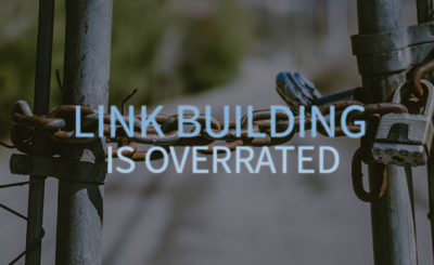 Link Building is Overrate is written over a chain locking a fence.